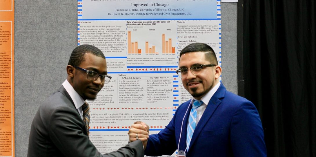 Students shake hands in front of research poster